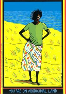Poster by Marie McMahon. The image shows a dark-skinned woman with her hands on her hips. She is wearing a green shirt and a patterned skirt. She is standing on yellow ground and there is a blue background of water and sky. On the sides of the artwork are yellow, red and black stripes forming the colours of the Aboriginal flag. On the bottom are the words: You are on Aboriginal land.
